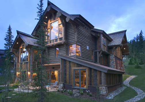Log accents blend with a variety of finishes for a rustic look to this hybrid log house in the mountains of Colorado.