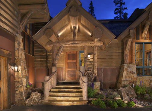 A very inviting entrance featuring log railings, flared cedar log butts, character log truss and log braces, natural stone and wood siding.