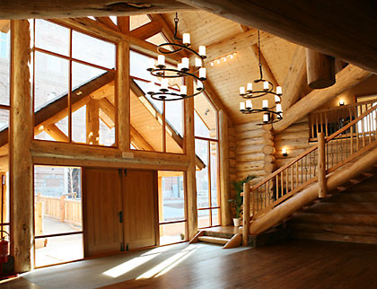 The front of the handcrafted log house is almost entirely windows framed by logs. Large dramatic spiral wrought iron chandeliers hang from the tall ceiling.