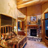 stone fireplace and log mantle in log home bedroom